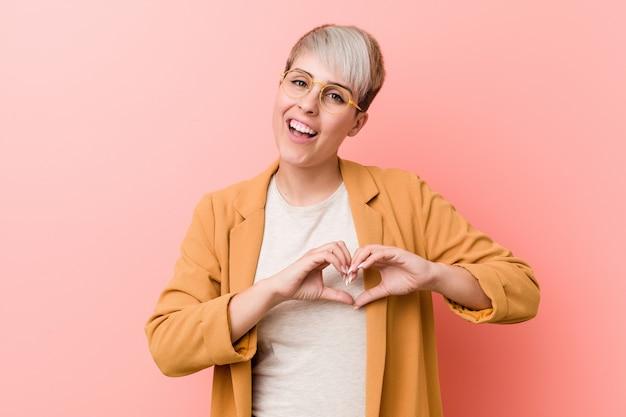 Jovem mulher caucasiana, vestindo uma roupa casual negócios sorrindo e mostrando uma forma de coração com as mãos.
