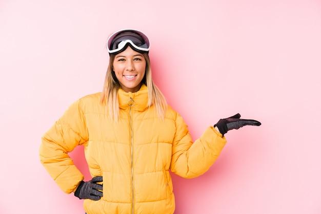 Jovem mulher caucasiana, vestindo uma roupa de esqui em rosa