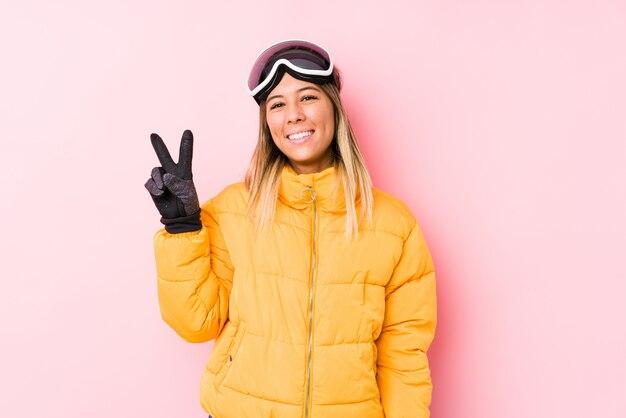 Jovem mulher caucasiana, vestindo uma roupa de esqui em uma parede rosa alegre e despreocupada, mostrando um símbolo de paz com os dedos.