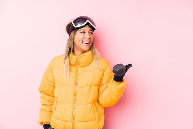 Jovem mulher caucasiana, vestindo uma roupa de esqui em uma parede rosa aponta com o dedo polegar, rindo e despreocupado.