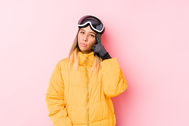 Jovem mulher caucasiana, vestindo uma roupa de esqui em uma parede rosa, apontando o templo com o dedo, pensando, focado em uma tarefa.