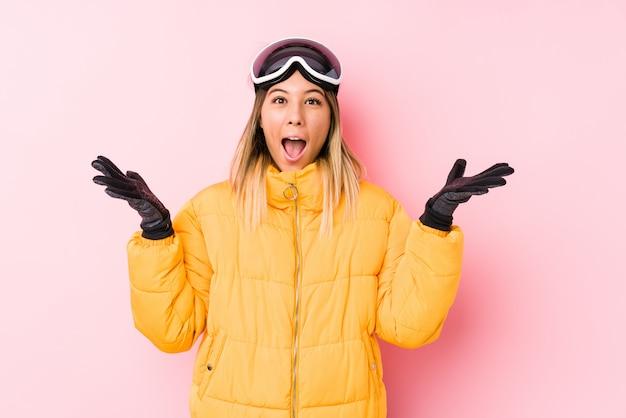 Jovem mulher caucasiana, vestindo uma roupa de esqui em uma parede rosa comemorando uma vitória ou sucesso, ele fica surpreso e chocado.