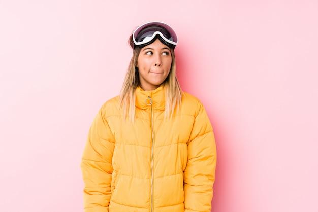 Jovem mulher caucasiana, vestindo uma roupa de esqui em uma parede rosa confusa, sente-se duvidoso e inseguro.