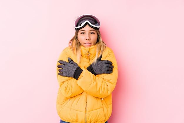 Jovem mulher caucasiana, vestindo uma roupa de esqui em uma parede rosa frio devido à baixa temperatura ou uma doença.
