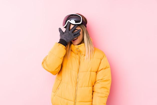 Jovem mulher caucasiana, vestindo uma roupa de esqui em uma parede rosa piscar através dos dedos, rosto de vergonha coberta.