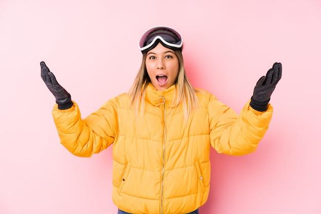 Jovem mulher caucasiana, vestindo uma roupa de esqui em uma parede rosa, recebendo uma agradável surpresa, animada e levantando as mãos.