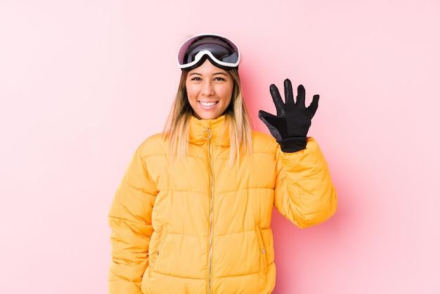 Jovem mulher caucasiana, vestindo uma roupa de esqui em uma parede rosa sorrindo alegre mostrando número cinco com os dedos.