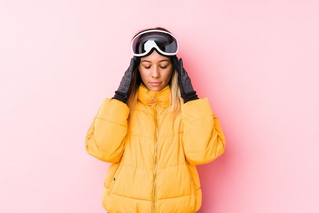 Jovem mulher caucasiana, vestindo uma roupa de esqui em uma parede rosa tocando templos e tendo dor de cabeça.