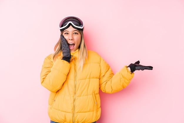 Jovem mulher caucasiana, vestindo uma roupa de esqui em uma rosa tem cópia espaço na palma da mão, mantenha a mão na bochecha. espantado e encantado.