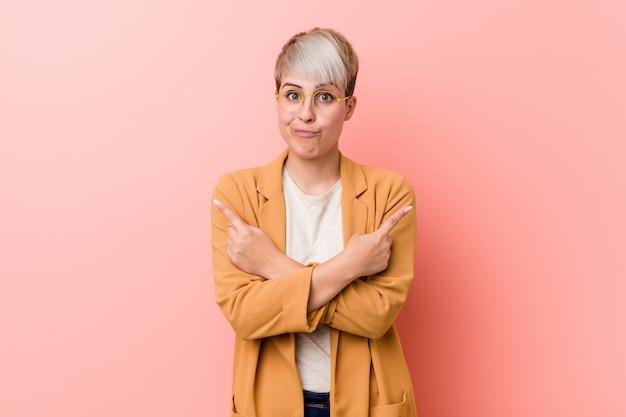 Jovem mulher caucasiana, vestindo uma roupa de negócios casuais aponta para o lado, está tentando escolher entre duas opções.
