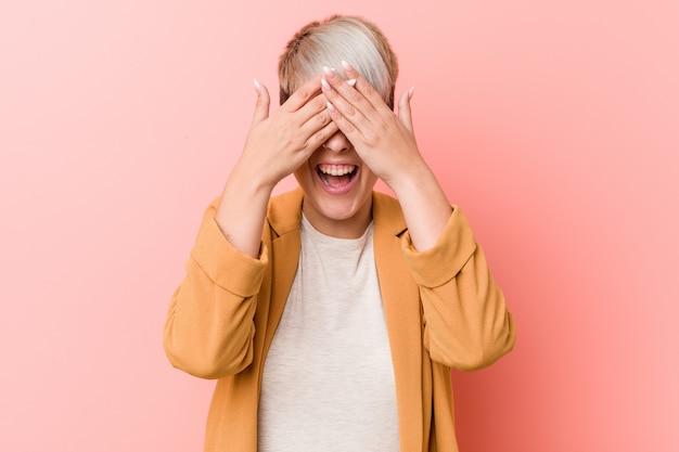 Jovem mulher caucasiana, vestindo uma roupa de negócios casuais cobre os olhos com as mãos, sorri amplamente esperando por uma surpresa.
