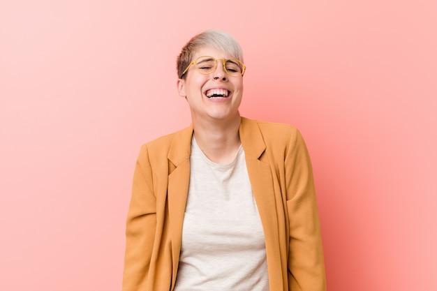 Jovem mulher caucasiana, vestindo uma roupa de negócios casuais ri e fecha os olhos, sente-se relaxado e feliz.