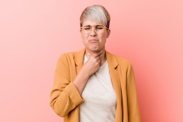 Jovem mulher caucasiana, vestindo uma roupa de negócios casuais sofre dor na garganta devido a um vírus ou infecção.