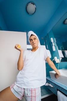 Jovem mulher caucasiana, vestindo uma toalha na cabeça e camiseta no banheiro, segure a maçã.