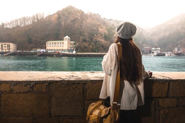 Jovem mulher caucasiana visitando uma cidade velha às margens do rio