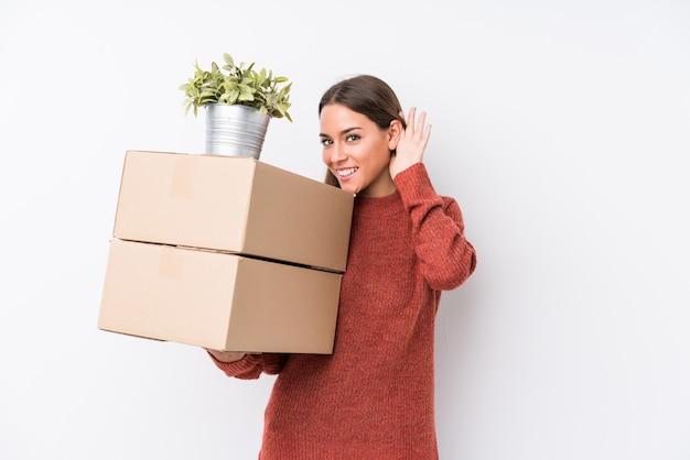 Jovem mulher caucasic segurando caixas isoladas tentando ouvir uma fofoca.