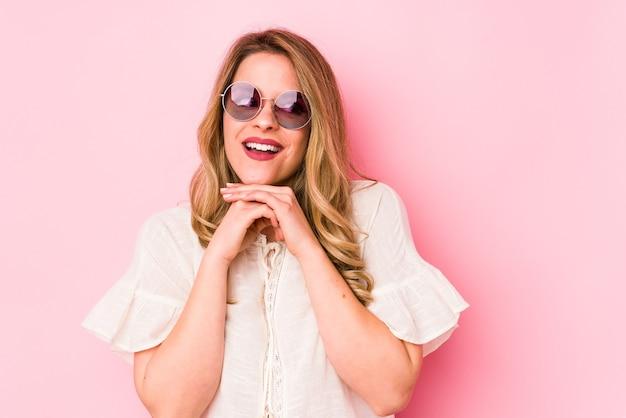 Jovem mulher cauciana com óculos isolados em um fundo rosa, orando pela sorte, espantada e abrindo a boca, olhando para frente.
