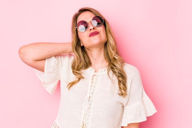 Jovem mulher cauciana com óculos tendo uma dor no pescoço devido ao estresse, massageando e tocando com a mão.