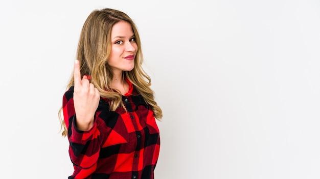 Jovem mulher cauciasiana isolada na parede branca apontando com o dedo para você como se fosse um convite para se aproximar.