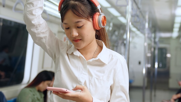 Jovem mulher celular no trem público conceito de deslocamento diário do estilo de vida urbano da cidade