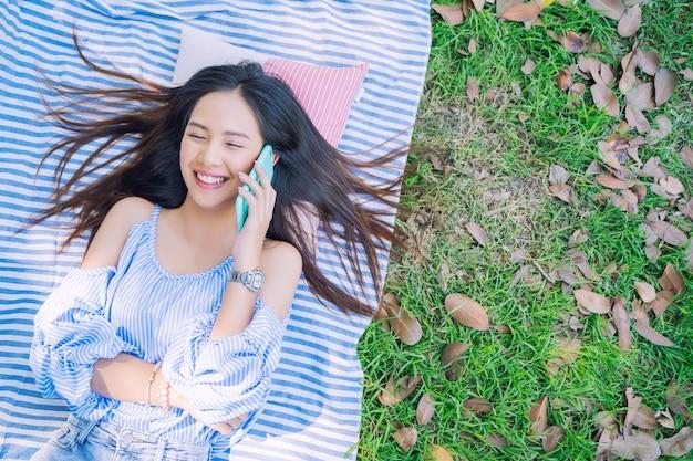 Jovem mulher chamando com smartphone no chão no jardim com feliz
