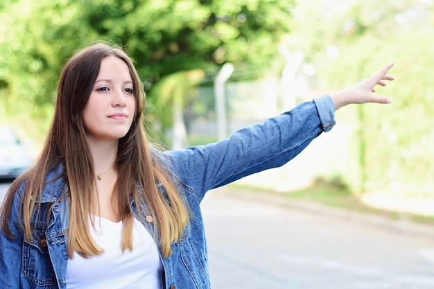 Jovem mulher chamando um táxi na rua.