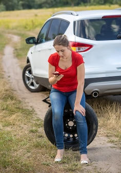 Jovem mulher chateada sentando em um pneu sobressalente ao lado de um carro quebrado no campo e pedindo ajuda