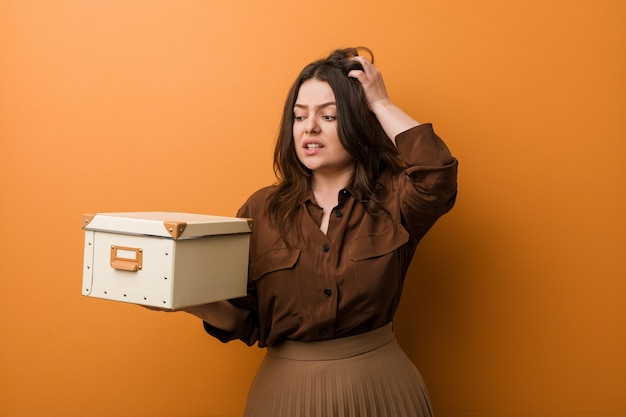 Jovem mulher cheia de curvas e tamanho segurando uma caixa sendo chocado, ela lembrou reunião importante.