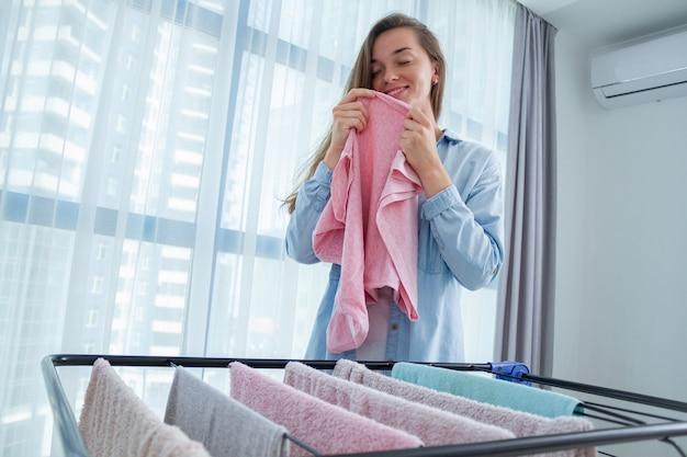 Jovem mulher cheirando a roupa limpa após a lavanderia em casa. usando secador de roupa após a lavagem. tarefas domésticas e tarefas domésticas