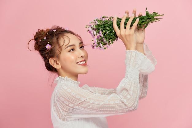 Jovem mulher cheirando um buquê de flores sorrindo