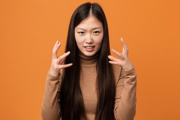 Jovem mulher chinesa bonita chateada, gritando com as mãos tensas.
