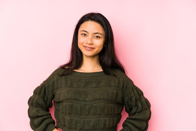 Jovem mulher chinesa confiante, mantendo as mãos nos quadris.