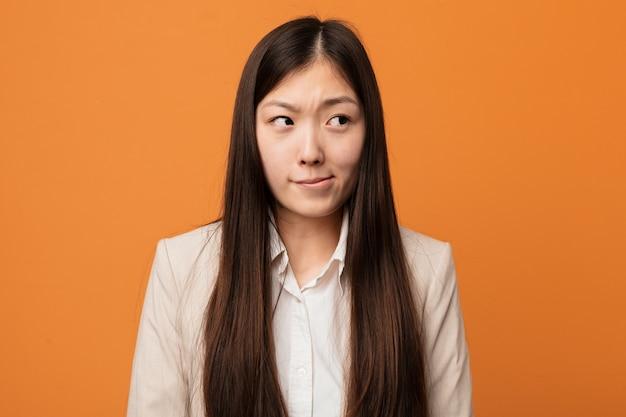 Jovem mulher chinesa de negócios confuso, sente-se duvidosa e insegura.