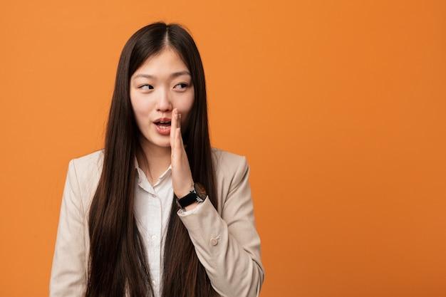Jovem mulher chinesa de negócios está dizendo uma notícia de frenagem quente secreta e olhando de lado