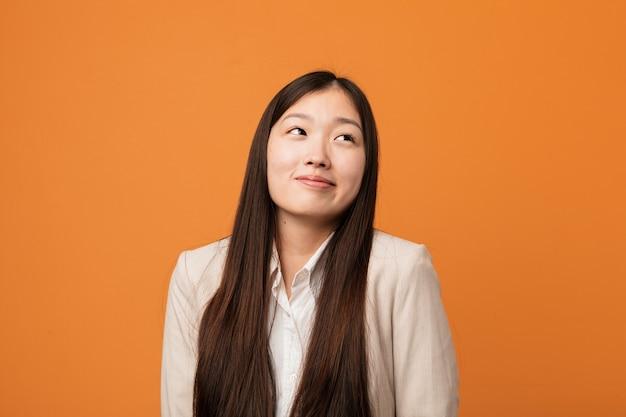 Jovem mulher chinesa de negócios sonhando em alcançar objetivos e propósitos