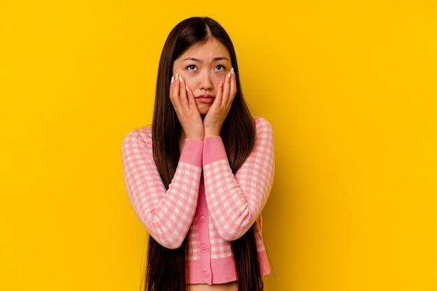 Jovem mulher chinesa isolada em um fundo amarelo, chorando e chorando desconsoladamente.