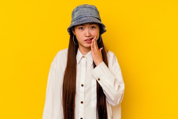Jovem mulher chinesa isolada na parede amarela, tendo uma forte dor nos dentes, dor molar.