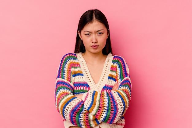 Jovem mulher chinesa isolada no fundo rosa, rosto carrancudo em desgosto, mantém os braços cruzados.