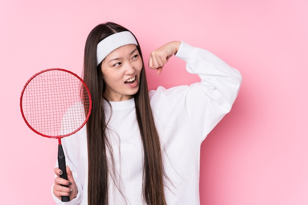 Jovem mulher chinesa jogando badminton isolado levantando o punho após uma vitória, o conceito de vencedor.