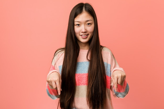 Jovem mulher chinesa legal aponta para baixo com os dedos, sentimento positivo.