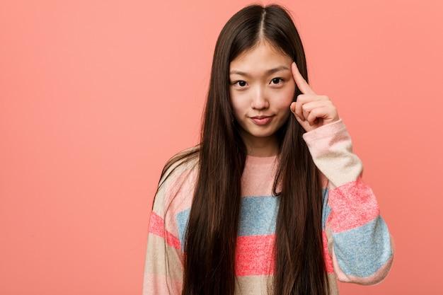 Jovem mulher chinesa legal apontando o templo com o dedo, pensando, focada em uma tarefa.