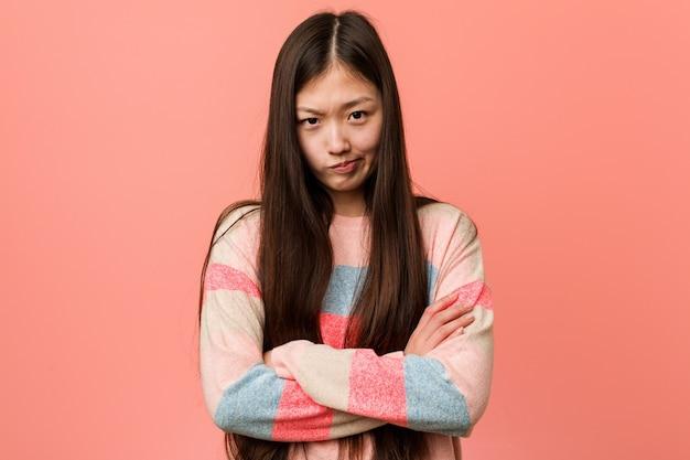 Jovem mulher chinesa legal, cara carrancuda em desprazer, mantém os braços cruzados.