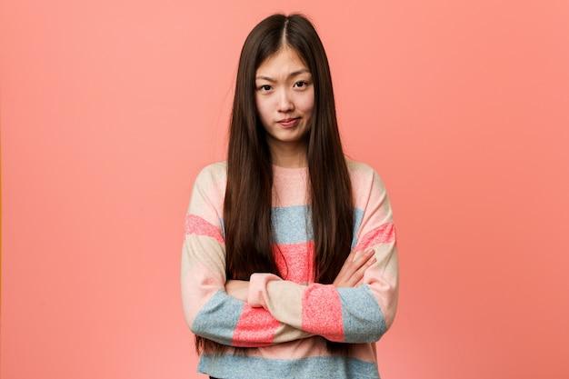 Jovem mulher chinesa legal infeliz olhando na câmera com expressão sarcástica.
