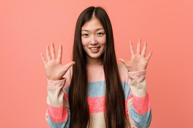 Jovem mulher chinesa legal mostrando o número dez com as mãos.