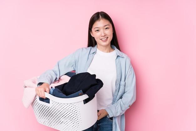 Jovem mulher chinesa pegando roupas sujas, isolada rindo e se divertindo.