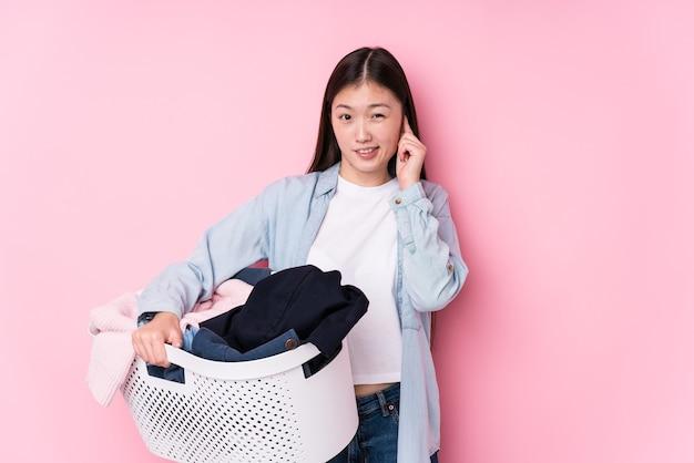 Jovem mulher chinesa pegando roupas sujas isoladas, cobrindo as orelhas com as mãos.
