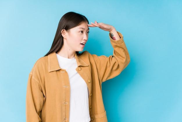 Jovem mulher chinesa posando em azul isolado, olhando para longe, mantendo a mão na testa.