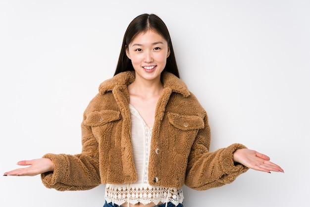 Jovem mulher chinesa posando em branco isolado, mostrando uma expressão de boas-vindas.