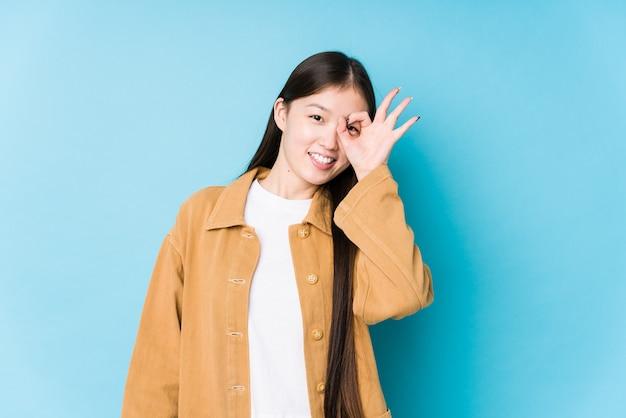 Jovem mulher chinesa posando em um fundo azul isolado animado, mantendo o gesto ok no olho.