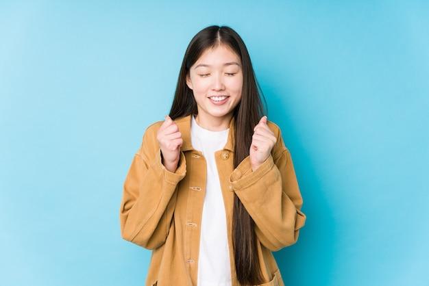 Jovem mulher chinesa posando em um fundo azul isolado levantando o punho, sentindo-se feliz e bem sucedido. conceito de vitória.